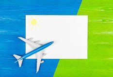 Model of airplane and blank sheet of paper on the blue and green wooden background. Travel concept. Creative design. Royalty Free Stock Photography