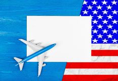 Model of airplane, blank sheet of paper and flag of USA on the blue wooden background. Travel concept. Stock Images