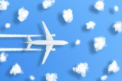 Model airplane design miniature on bight blue background with fluffy clouds and shadows objects. The idea of tickets for the trip royalty free stock photography