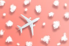 Model airplane design miniature on bight living coral background with fluffy clouds and shadows objects. The idea of tickets for stock images