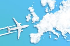 Model airplane design miniature blue background fluffy clouds in the shape of continent Europe. The idea of tickets for the trip, royalty free stock photo