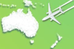 Model airplane design miniature green background fluffy clouds in the shape of continent Australia New Zealand. The idea of stock images