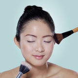 Model apply makeup on blue background Stock Photos
