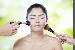 Model apply makeup by her assistant Stock Photos