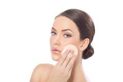 Model applying foundation on her face Stock Image