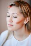 Model while applying makeup, contouring cheekbones. Royalty Free Stock Image