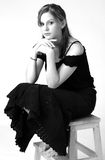 Model in B&W 8. Model in black dress, sitting on stool, on white background Royalty Free Stock Images