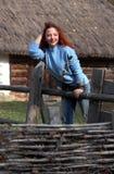 model barn En kvinna med rött hår ser bort och står på ett trästaket i parkerar Försiktigt rätar ut handen hår royaltyfria foton