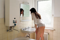 Model in Bathroom. Woman looking at mirror in an old bathroom stock photography