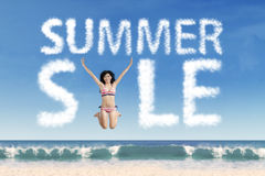 Model at beach with summer sale cloud Royalty Free Stock Images