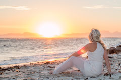 Model on beach at sunset. Model on sitting on beach looking at sunset over the ocean stock photo