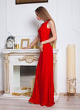 Model with beautiful long hair posing in red dress. Royalty Free Stock Images
