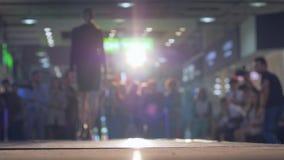 Model beszcześci wybieg w sukni i szpilki podczas seans nowej kolekcji odziewają w oświetleniu zbiory