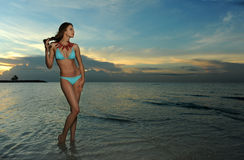 Model in bikini with coral necklace posing sexy on the empty beach. During sunrise Royalty Free Stock Image