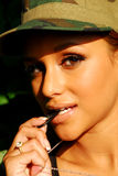 Model biting a dogtag. Beautiful model wearing a camouflage hat Stock Photography