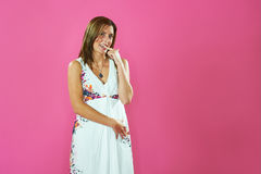 Model biting the finger on pink background Royalty Free Stock Photography