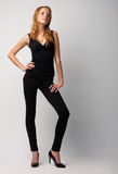 Model In Black. Full length portrait of a young red-haired model dressed in black, posing over white Stock Photo