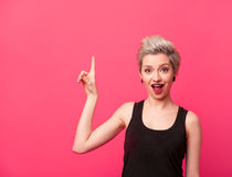 Model with blond short hair pointing up on pink. Fashion Model with blond short hair In Black top pointing up with amazed face expression. Surprised hipster royalty free stock images