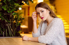 Model with blonde long hair and bright pink lipstick in white sweater sitting on a chair in a cafe with beautiful stylish interior Stock Photo