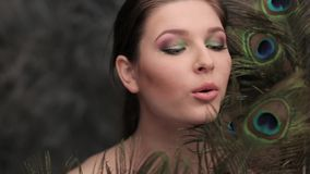 Model blowing on the peacock feather stock video