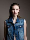 Model in blue denim jeans jacket. Close up portrait of a beautiful female fashion model in blue denim jeans jacket posing on gray background Stock Photography