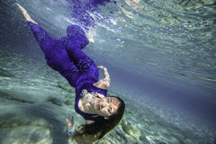 Model in blue dress diving. Young female model in blue dress diving stock photo