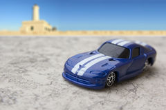 Model of blue sports car. Toys: Blue sports car model with lighthouse in the background Royalty Free Stock Image