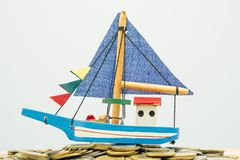Model boat is placed on a pile of coins.using as background business concept and finance concept with copy spaces for your text o. R design stock photography