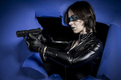Model, Brunette in black latex costume with pistol over broken p Stock Photography