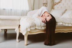 Model brunette woman in white translucent cloak lying in bed Stock Photos