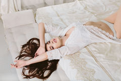 Model brunette woman in white translucent cloak lying in bed Stock Photo