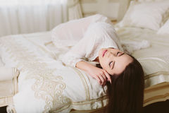 Model brunette woman in white translucent cloak lying in bed Stock Photography