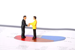 Model business figures pie chart D. Photograph of model business figures shaking hands on a pie chart Royalty Free Stock Images