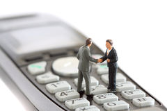 Model business figures telephone A. Photograph of model business figures shaking hands on a telephone. Telephone sales concept Royalty Free Stock Images