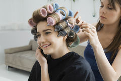 Model On Call While Having Hair Curled Stock Image