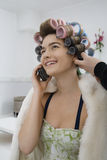 Model On Call While Having Hair Curled Royalty Free Stock Images