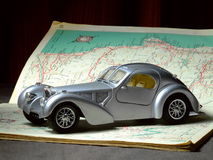 Model Car on Road Map. A scale model of a 1936 Bugatti Atlantique sitting on an old book of road maps Royalty Free Stock Photo