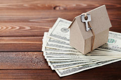 Model cardboard home, key and dollar money. House building, insurance, housewarming, loan, real estate, cost of housing, buying. Model of cardboard home with key Stock Image