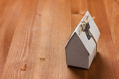 Model of cardboard house with a bow of twine and key.  Royalty Free Stock Photo