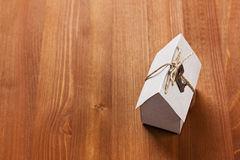 Model of cardboard house with a bow of twine and key. Royalty Free Stock Images