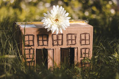 Model of cardboard house with flower. Model of cardboard house with a bow of twine and key against green bokeh background. house building, loan, real estate or Stock Images