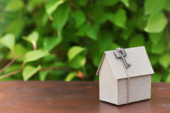 Model of cardboard house with key against green leaves background. Purchase, rent and construction country real estate concept. Stock Images
