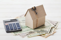 Model of cardboard house with key, calculator and cash dollars. House building, loan, real estate. Cost of public utilities. royalty free stock images