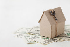 Model of cardboard house with key and dollar bills. House building, loan, real estate, cost of housing or buying a new home concep. T Stock Image