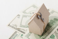 Model of cardboard house with key and dollar bills. House building, loan, real estate, cost of housing or buying a new home concep Stock Photos