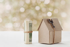 Model of cardboard house with key and dollar bills. House building, loan, real estate, cost of housing or buying a new home concep Royalty Free Stock Photography