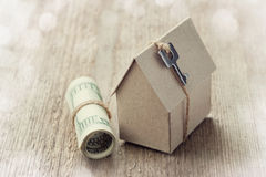 Model of cardboard house with key and dollar bills. House building, loan, real estate, cost of housing or buying a new home concep Royalty Free Stock Images