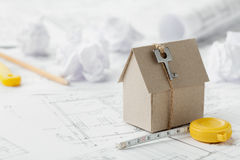 Model cardboard house with key and tape measure on blueprint. Home building, architectural and construction design concept. Model of cardboard house with key and Royalty Free Stock Image
