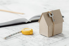 Model cardboard house with key and tape measure on blueprint. Home building, architectural and construction design concept Royalty Free Stock Image