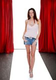 Model on the catwalk. Brunette fashion model on the catwalk with red drapes Royalty Free Stock Photo